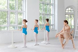 picture of ballet barre  - Three little ballerinas with personal classic ballet teacher in dance studio posing at ballet barre on a white background - JPG