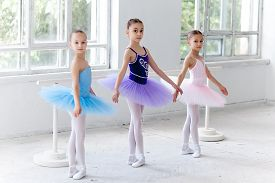 pic of ballet barre  - Three little ballet girls in multicolored tutu posing at ballet barre together on white background - JPG