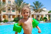 picture of floaties  - Happy young boy wear floaties poolnside at a tropical resort - JPG