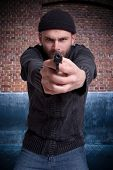 Dangerous looking man holding a gun aiming at you in an urban background