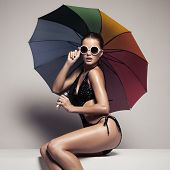 Beautiful woman in stylish black swimwear and sunglasses holding colorful umbrella. Perfect slim tan poster