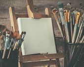 Artistic Equipment: Empty Artist Canvas On Easel And Paint Brushes In A Artist Studio. Retro Toned P poster