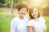Portrait of attractive Asian elderly mother and daughter, senior adult woman and grown child. Outdoo poster