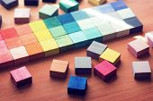 Selection of colors. colorful  color sample cubes arranged on a wooden table. Focus on foreground. poster