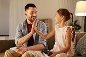 family, gaming and entertainment concept - happy father and little daughter with gamepads playing vi poster