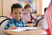 Cute African American boy doing homework in classroom at school poster