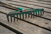Old Rake On The Background Of The Wooden Planks. Rake On The Wooden Plank Floor. poster