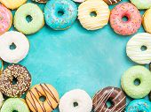 Top View Of Assorted Donuts On Blue Concrete Background With Copy Space. Colorful Donuts Background. poster