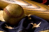 stock photo of baseball bat  - A vintage or antique baseball and baseball bat on American flag bunting - JPG
