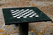 stock photo of draught-board  - Green marble chess board table in park - JPG