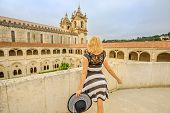 Blonde Caucasian Tourist Woman Looking At Mosteiro De Santa Maria De Alcobaca. Tourism And Travel In poster