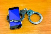 Handcuffs And Mobile Phone On The Wooden Table Closeup poster