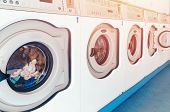 Row Of Industrial Laundry Machines In Commercial Laundromat. Concept Business Washer Shop. poster