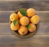 Top View. Ripe Apricots On Rustic Background. Bowl With Apricots With Leaves On Wooden Background. R poster