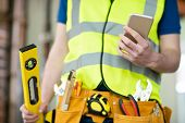 Detail Of Construction Worker On Building Site Wearing Tool Belt Using Mobile Phone poster
