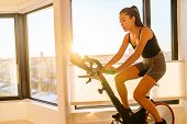 Home fitness workout woman training on smart stationary bike indoors watching screen connected onlin poster