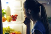 foto of refrigerator  - Young woman craving food choosing near refrigerator at night - JPG