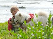 picture of laika  - A boy plays with a dog breed husky - JPG