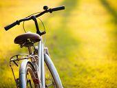 ein Fahrrad in Wiese während des Sonnenuntergangs