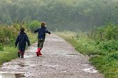 stock photo of rainy day  - Two brothers splashing in puddles on rainy day - JPG