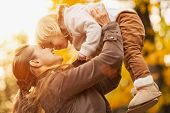 image of throw up  - Young happy mother rising baby girl up - JPG