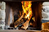 fire in a rustic fireplace in a traditional mountain hut