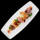 Medium rare fried duck breast in plate isolated on black - modern czech cuisine