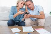 foto of receipt  - Worried couple going over their debt at home on sofa - JPG