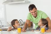 Father talking to his children while they are having breakfast in the kitchen