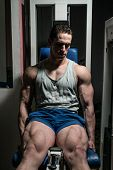 Bodybuilder Doing Heavy Weight Exercise For Legs On Machine Leg Extensions