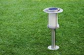 Lámpara solares sobre fondo verde hierba.