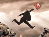 Businessman jumping between two rocks