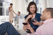 Parejas multiétnicas bebiendo vino en la sala de estar