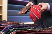 Closeup midsection of a businessman selecting ties in clothes store