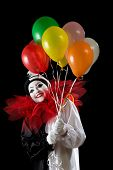 Happy female Pierrot clown holding colorful balloons