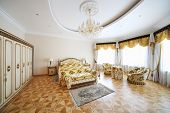 Bedroom with beautiful double bed, wardrobe and armchairs in classic style.
