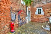 Small courtyard among old red brick walls with graffiti in Venice, Italy.