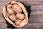 Unwashed potatoes in a black and brown paper sack, against wood background
