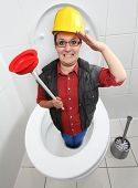 stock photo of plunger  - Funny repairman with red toilet plunger cleaning the toilet bowl - JPG