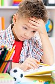 stock photo of adolescent  - Portrait of despairing adolescent boy in school classroom - JPG