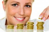 foto of precaution  - a woman stacks coins - JPG