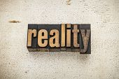 reality word in vintage letterpress wood type on a grunge painted barn wood background