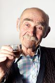 foto of glass-wool  - Portrait of cheerful old man with blue eyes making a toast - JPG