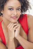 A beautiful mixed race African American girl or young woman wearing a red dress looking happy and smiling