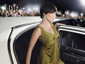 Beautiful young woman in evening wear getting out of limousine in front of fans and paparazzi