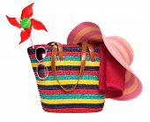 Bolsa de praia listrado colorido com um óculos de sol toalha de chapéu de palha e um moinho de vento brinquedo