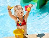 Child with bucket in swimming pool.  Summer outdoor.