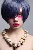 Portrait of young beautiful woman with fancy bright make-up and cosplay wig