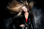 stock photo of hair motion  - fashion blond model with flying hair studio dark background.