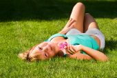 Young Smiling Girl Lies On Grass On The Back